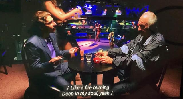 hesh rabkin is talking to christopher moltisanti while sitting down at the bada bing club.