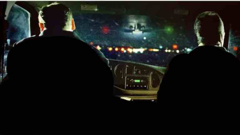 tony soprano and dwight harris are sitting in the car near an airport on a cold and snowy night.