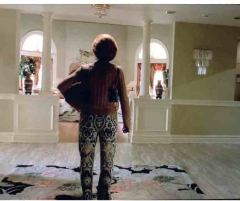 carmela soprano is standing all alone in her house.