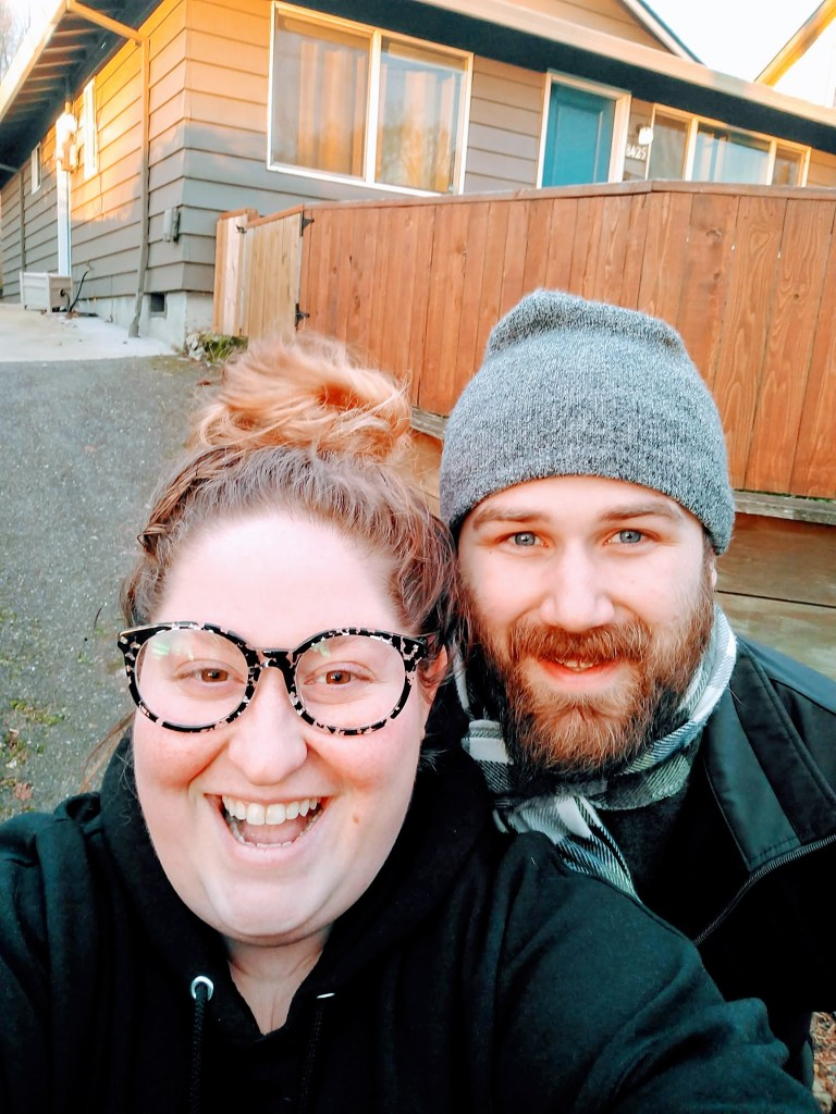 Sorcha and Matt standing in front of their sold home the day they left Portland. They both look tired, but excited and happy. Both are wearing black jackets and Matt has a green and white plaid scarf and a grey beanie. Sorcha has on black and white round glasses and her red curly hair is in a bun.