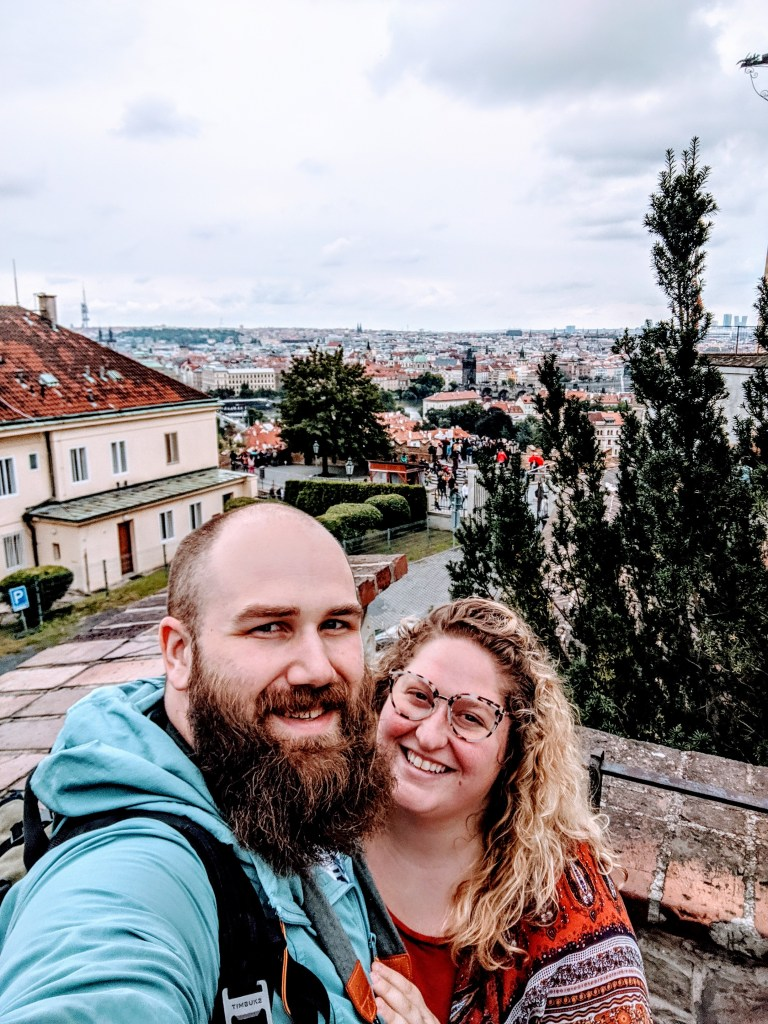 Sorcha and Matt at the Prague Castle  in Czech Republic overlooking the old town. Sorcha is wearing an orange patterned top, tortoise cat eye glasses. Matt is wearing a teal and mulberry LL Bean hoodie and has a full beard and shaved head. Both are smiling broadly.