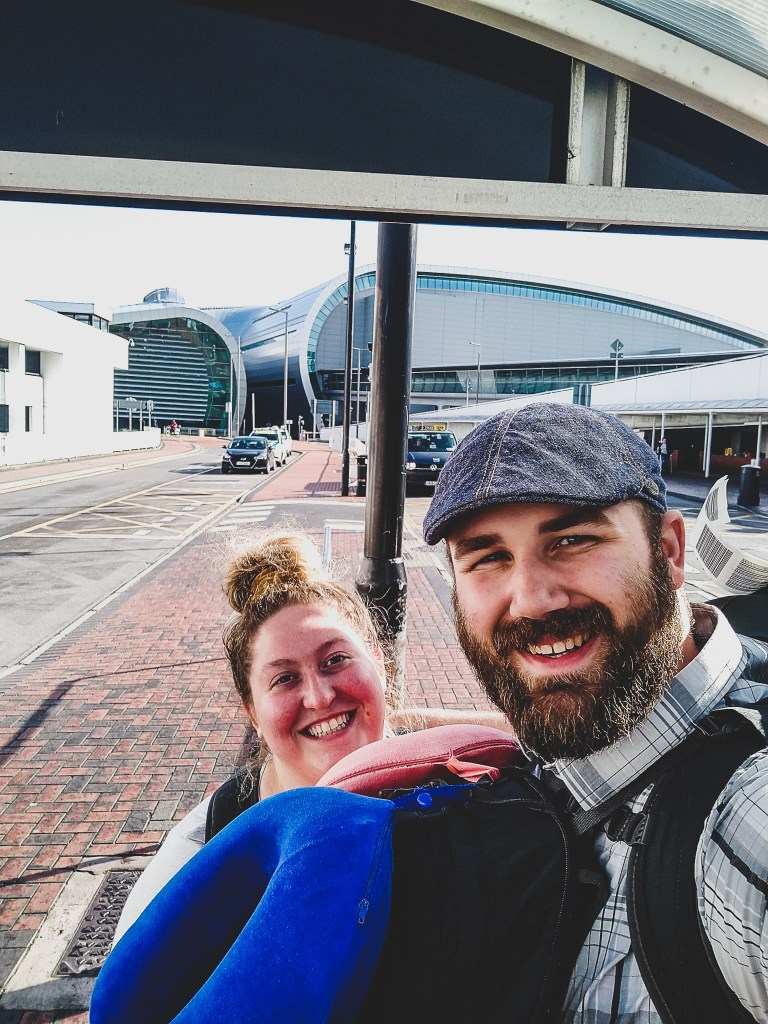 Sorcha and Matt in front of Dublin International Airport wearing their Osprey Farpoint Backpacks, neck pillows and looking very tired from their trip from Rome to Dublin.