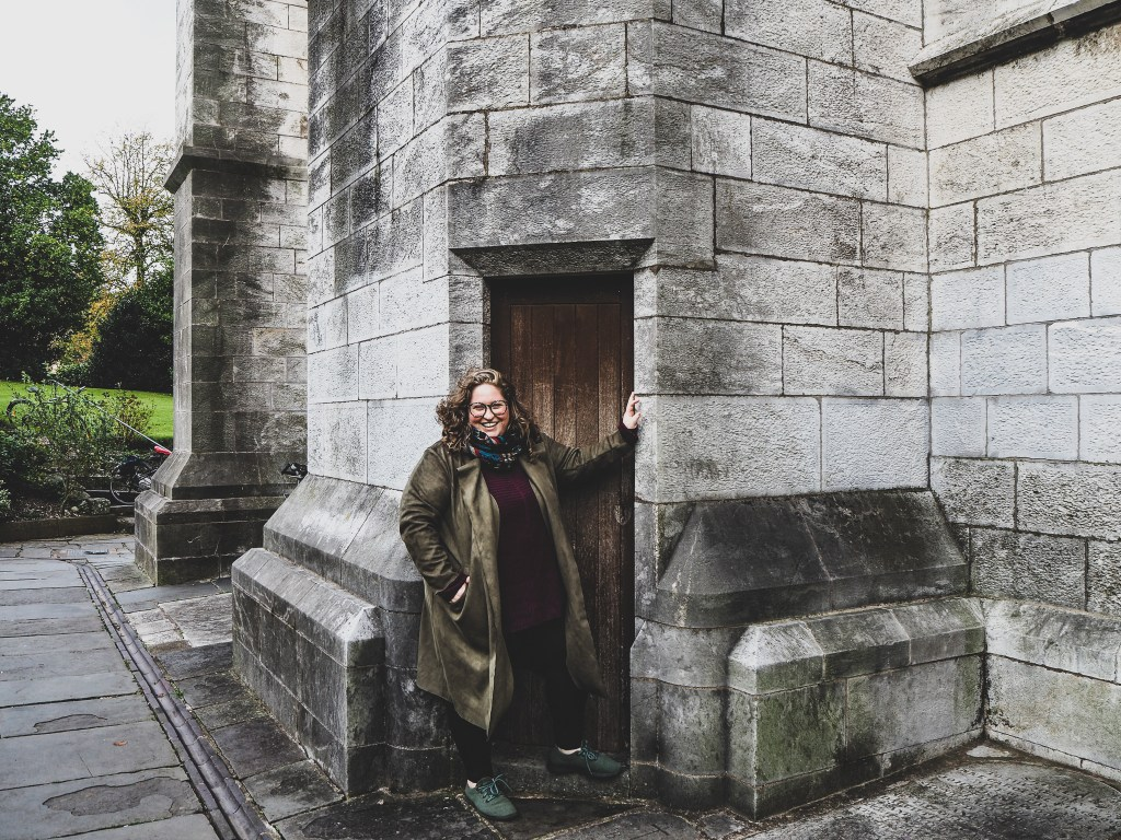 Sorcha smiling in front of a small wooden door outside of the grey stone building of St. FinnBarres Cathedral in Cork Ireland. She's wearing an olive color faux sued longline jacket, burgundy oversized sweater, black leggings, her allbirds, and her navajo infinity scarf. Her left hand is touching the doorway and she's smiling broadly at the camera.