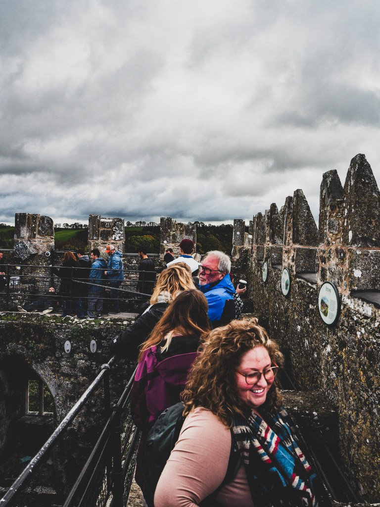Sorcha Smiling and looking through a window in the walls of Blarney Castle. Steps from the Blarney stone. She has her hair down, and curly, is wearing taupe oversized round glasses a taupe long sleeved top, and a navajo print infinity scarf and is smiling.