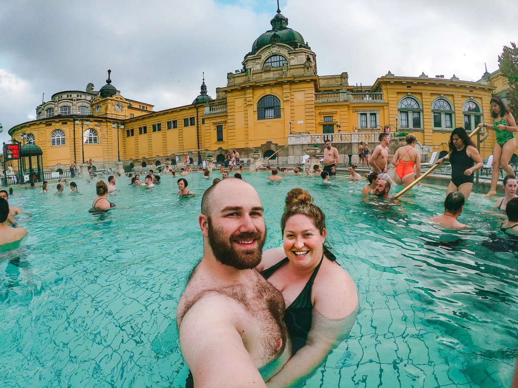 Sorcha and Matt at the Szechenyi Spas, surrounded by steaming warm water, the golden palace in the backdrop.