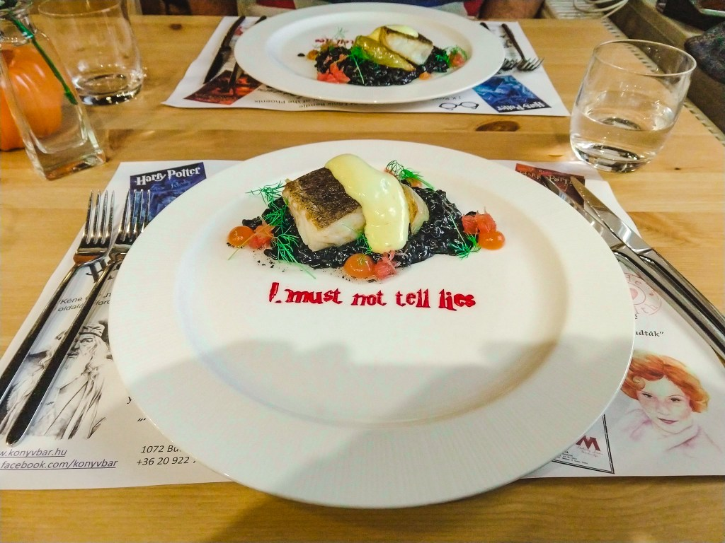 "Grilled cod fish on a bed of octopus ink risotto, garnished with fennel and grapefruit pearls and a hollandaise sauce. On the plate in red edible ink is the words ""I must not tell lies"""