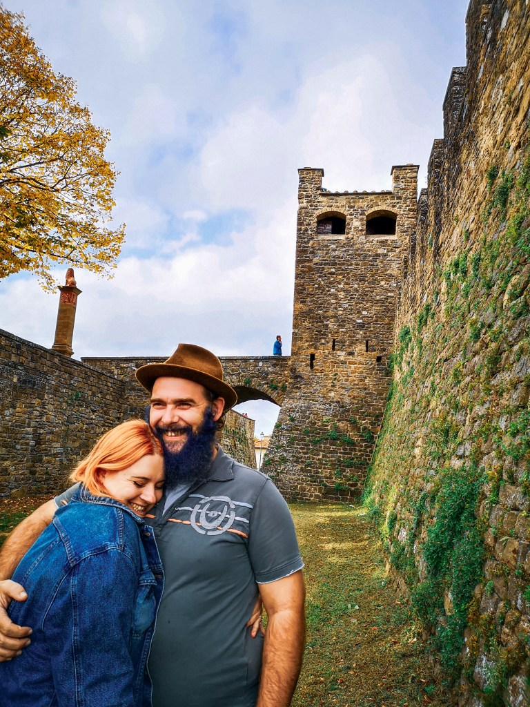 Jenn, who has peachy blonde hair, left, wearing denim jacket with Hen right, wearing grey collared shirt, arm around Jenn with beard and fedora, both smiling in front of stone castle in Bratislava.