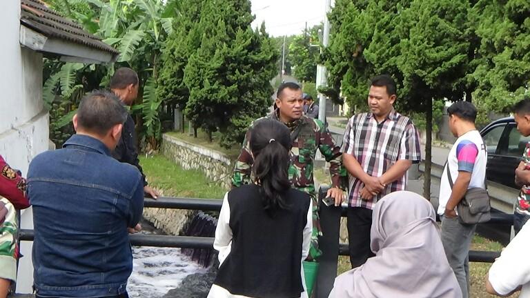 Dansektor 21 Satgas Citarum Harum saat berkumpul dengan para perwakilan perusahaan di Jl Industri, Kota Cinahi, dengan latar belakang aliran sungai yang pekat akibat limbah.