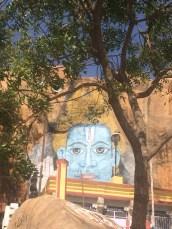 Painted deity on rocky hill peeking through tree branches