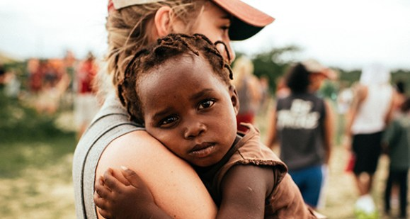 Woman gently holding vulnerable child