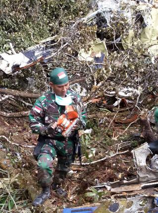An Indonesian soldier carries the flight recorder from the Trigana Air Service ATR 42-300 crash site near Oksob village, Bintang Mountains district, Papua province, Indonesia, August 18, 2015 in this military handout photo provided by Antara Foto. REUTERS/Pendam Cenderawasih/Antara Foto