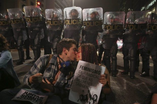 epa05341213 A couple of Brazilian activists kiss in front of riot police during a rally against the gang rape of 16-year-old girl in a Rio de Janeiro shantytown, in Sao Paulo, Brazil, 01 June 2016. The girl told police she was drugged and that she awoke to find herself surrounded by 33 men armed with rifles and handguns. Two of the men accused in connection with the gang rape were arrested on 30 May. EPA/SEBASTI¿O MOREIRA
