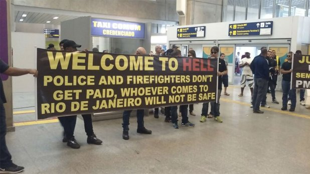 """A """"Welcome to Hell"""" sign was held up outside Rio's airport as tourists arrived. Photo: Twitter/Michael Smith"""