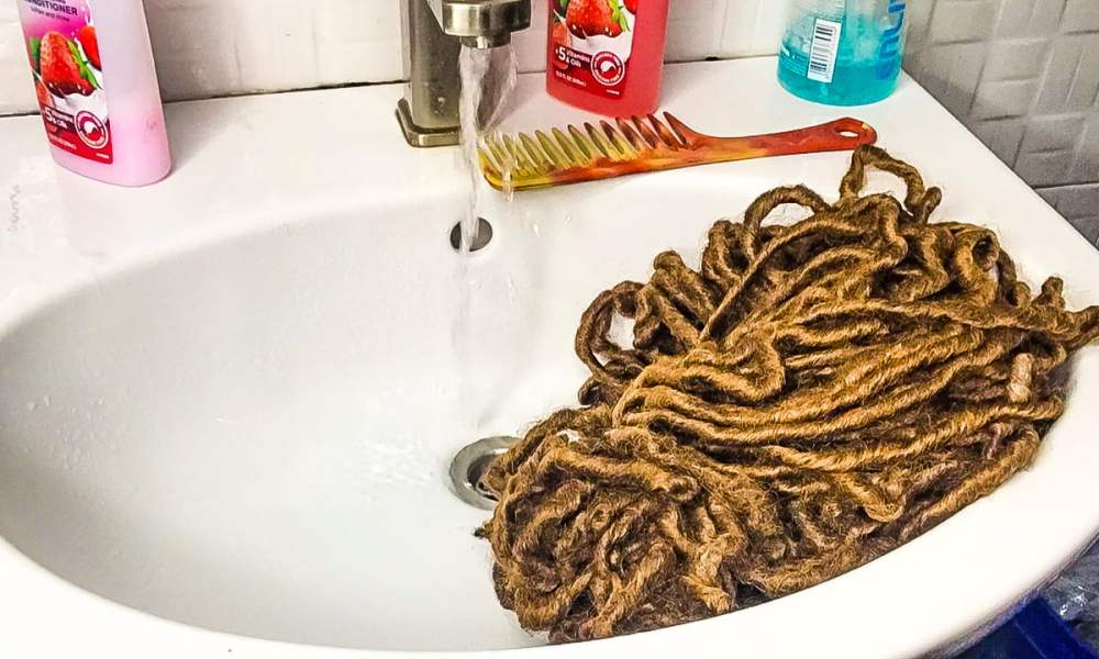 running water over crochet hair extesions surrounded by shampoo, conditioner and a comb on a water basin in a bathroom