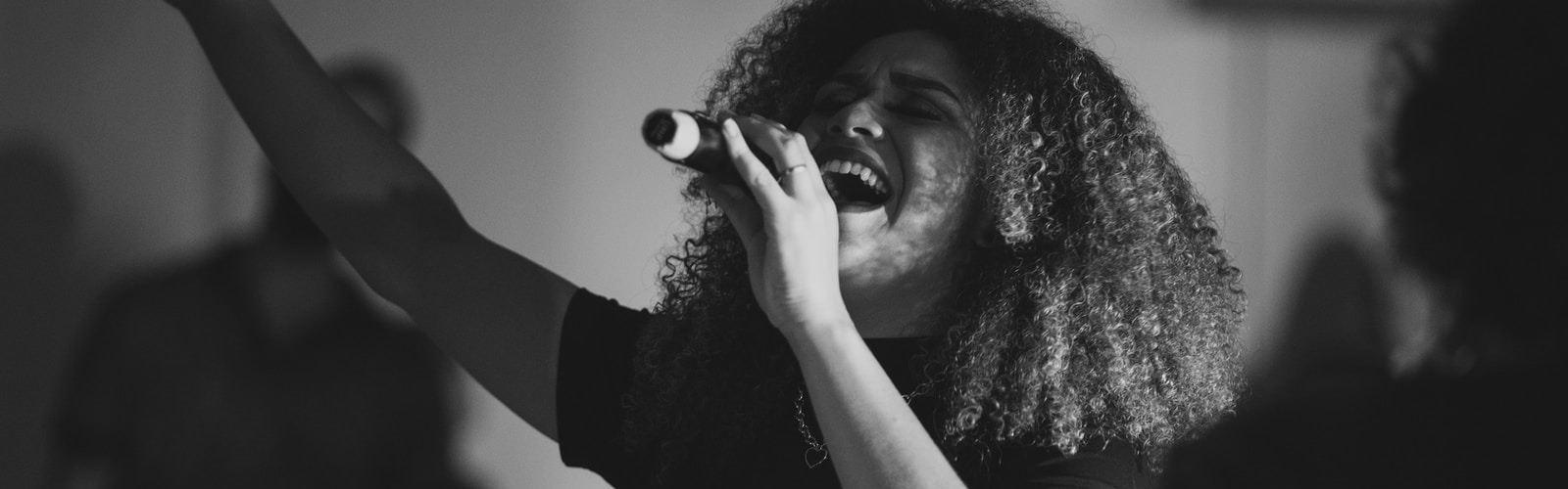woman in black tank top singing