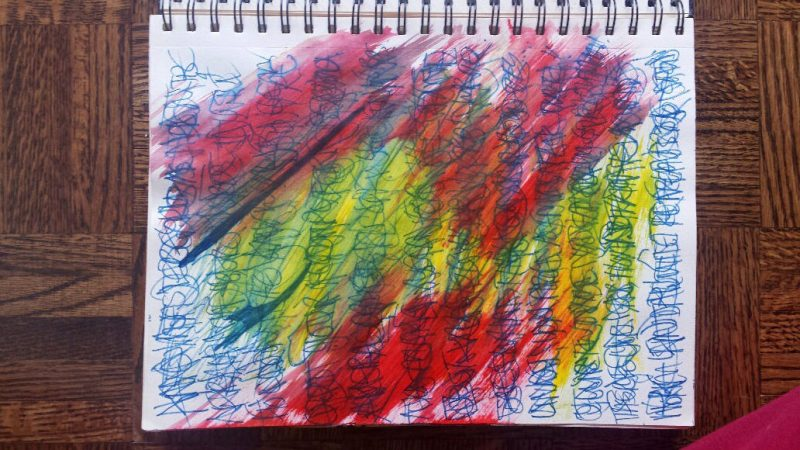 art journal page with red, yellow, orange paint over words in blue felt pen