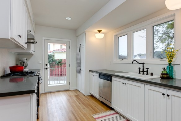 Galley kitchen with stainless steel appliances, quartz counters and hex tile backsplash