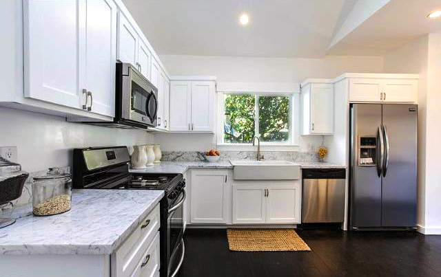 Kitchen with marble counters, farmhouse sink and stainless steel appliances