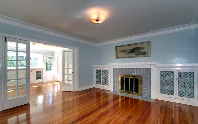 Living room with original wood floors, built-in cabinets and fireplace