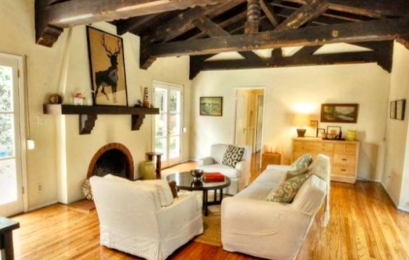 Living room with original wood floors, beamed ceiling and fireplace