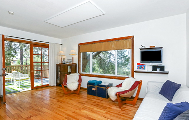Living room with wood floors and view deck