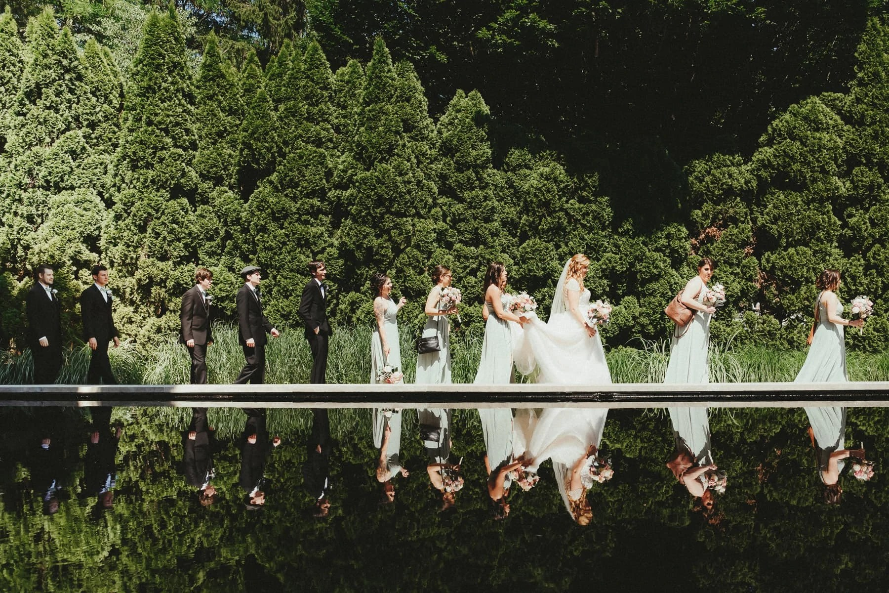 bridal Party walking across with reflection in the pond