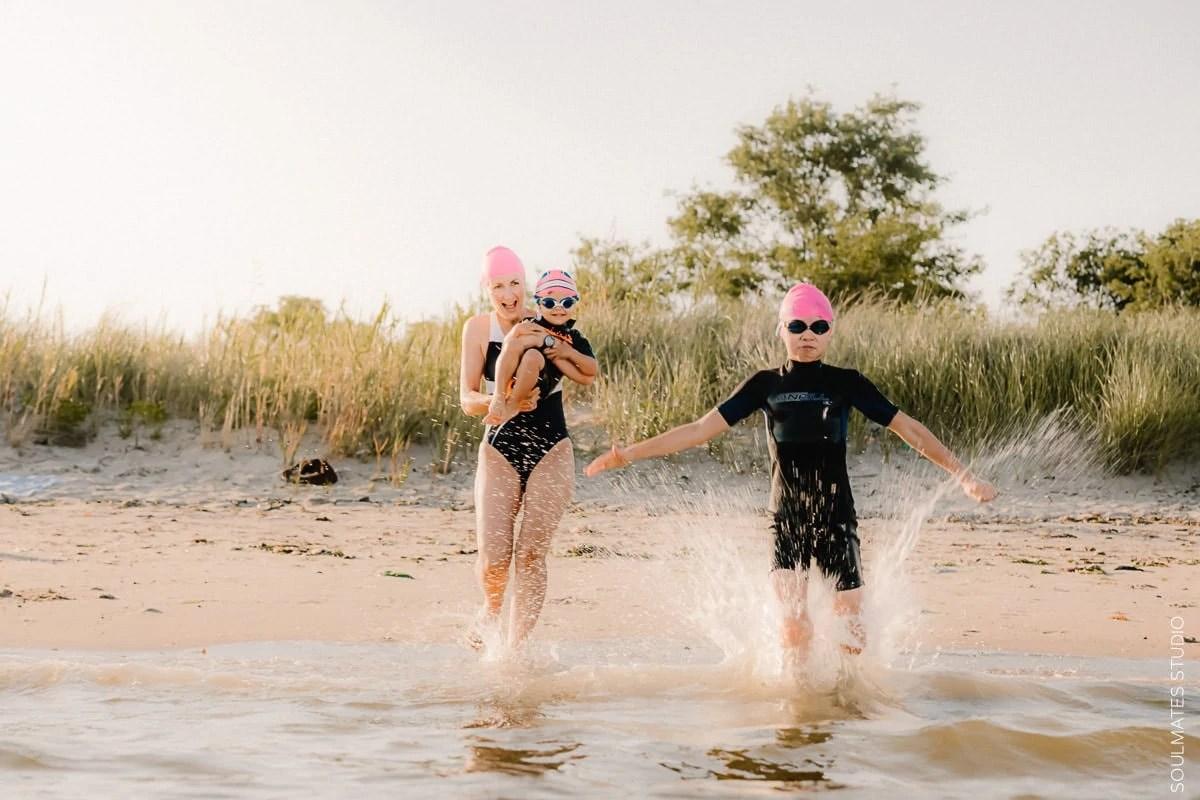 New York Family fun beach photo. Mum and small children running towards the ocean