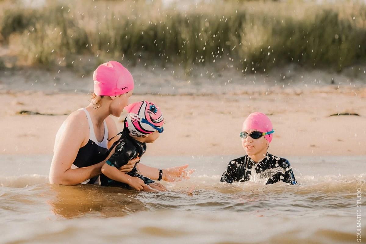 New York Family fun beach portrait. Mum and children playing in the ocean