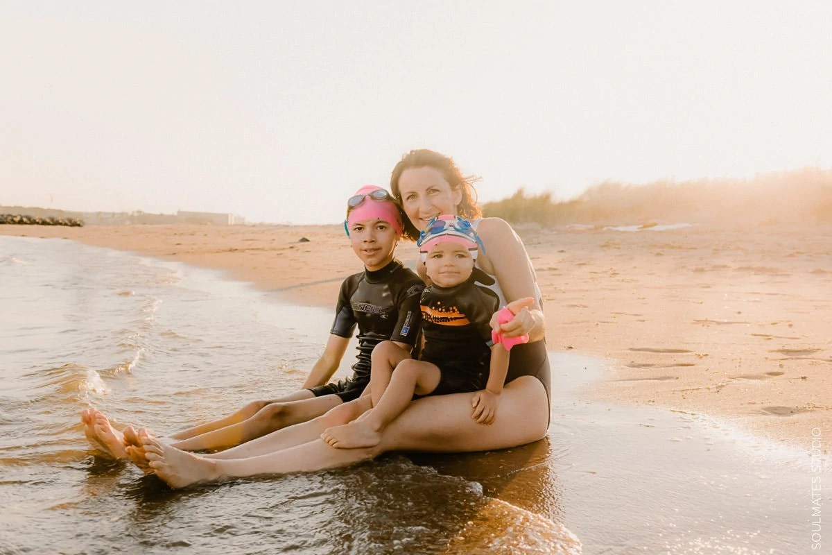 New York Family lifestyle portrait. Mum sitting with her children on the beach