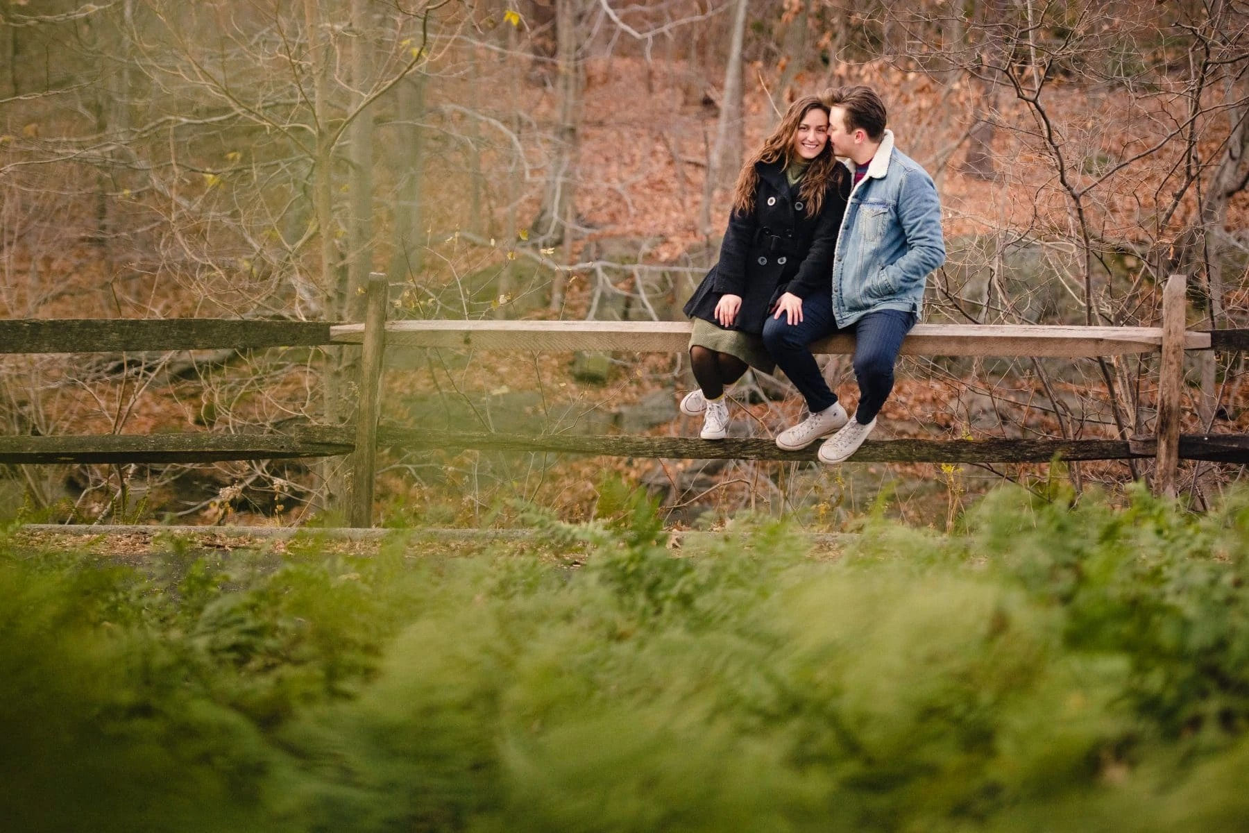 Happy Couple in love sitting on a wooden fence at Bronx Botanical Garden