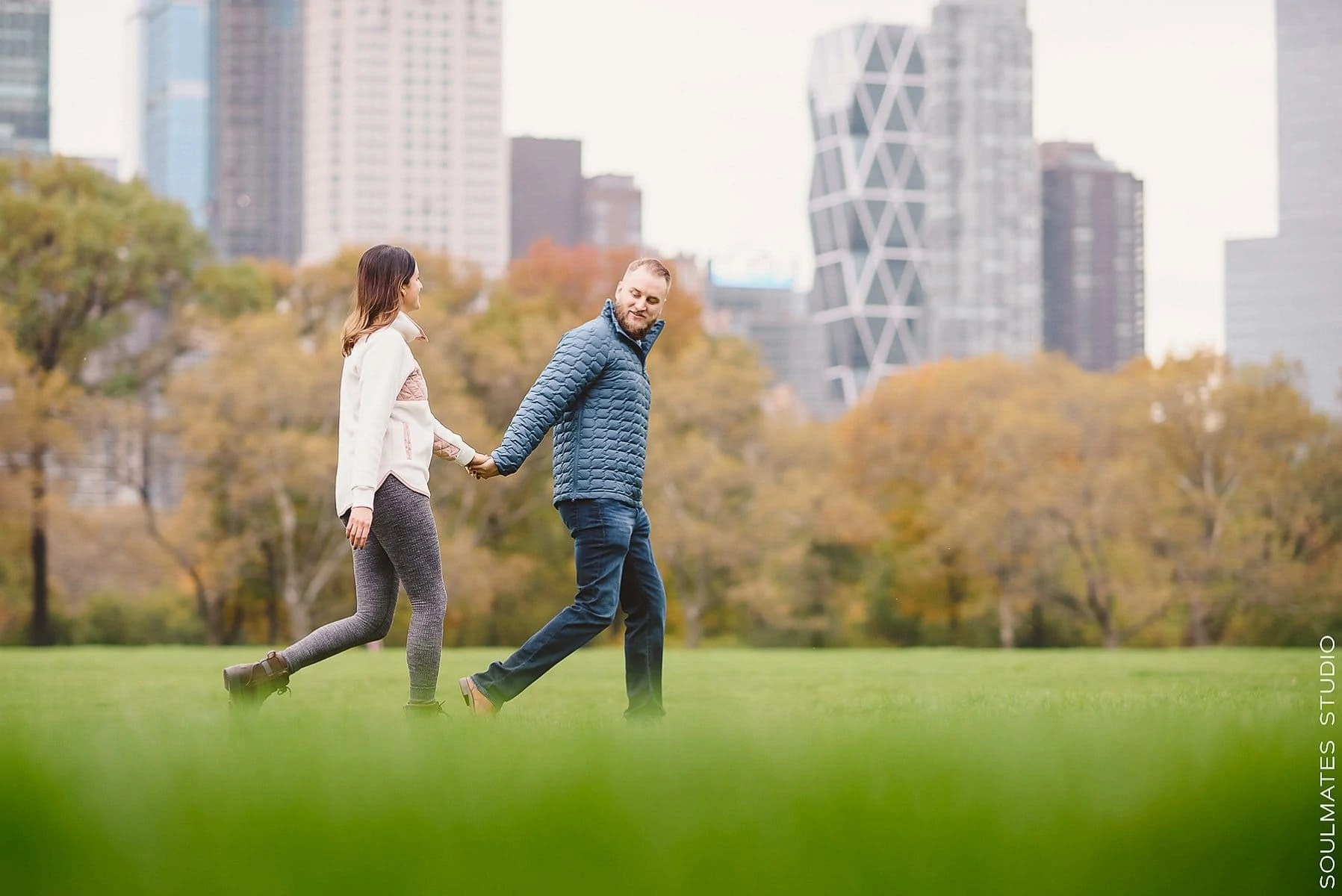 Couple walking on the grass during New York engagement