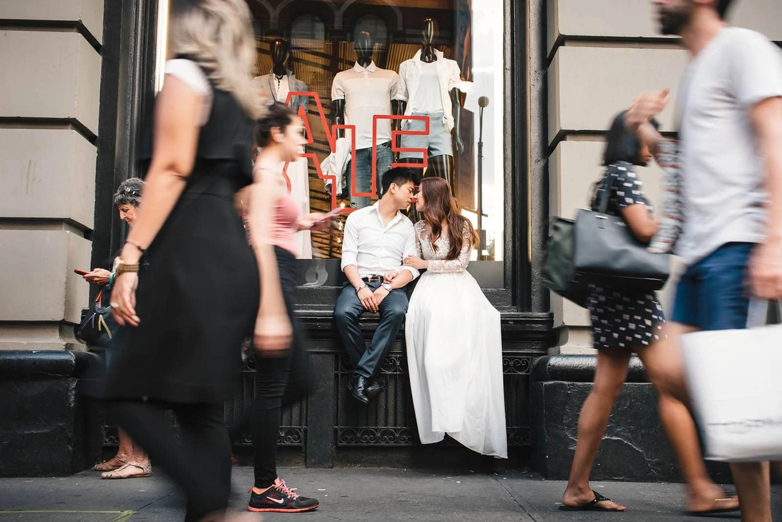 Manhattan East Village engagement Couple sitting on the storefront window