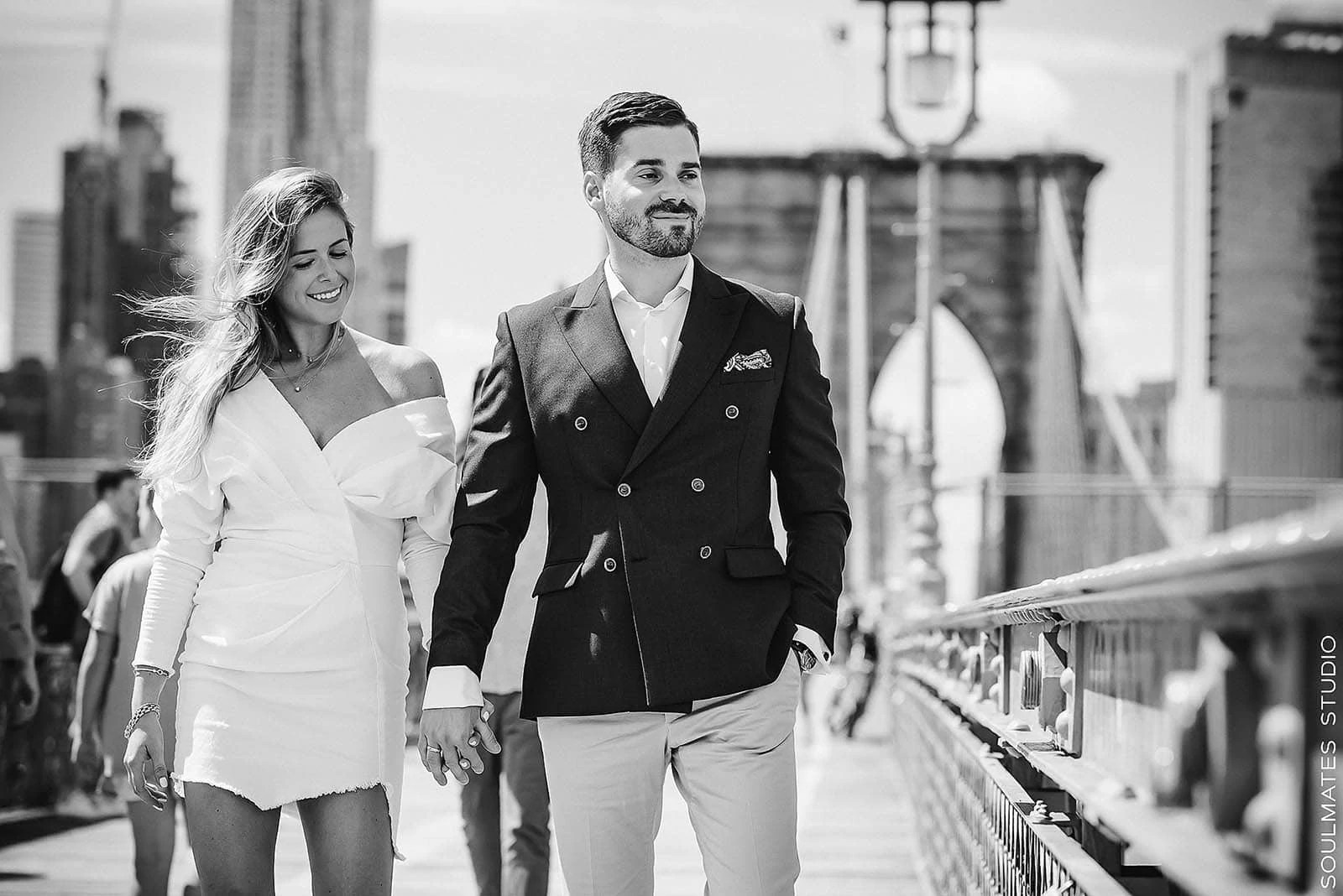 Couple smiling on the Brooklyn Bridge