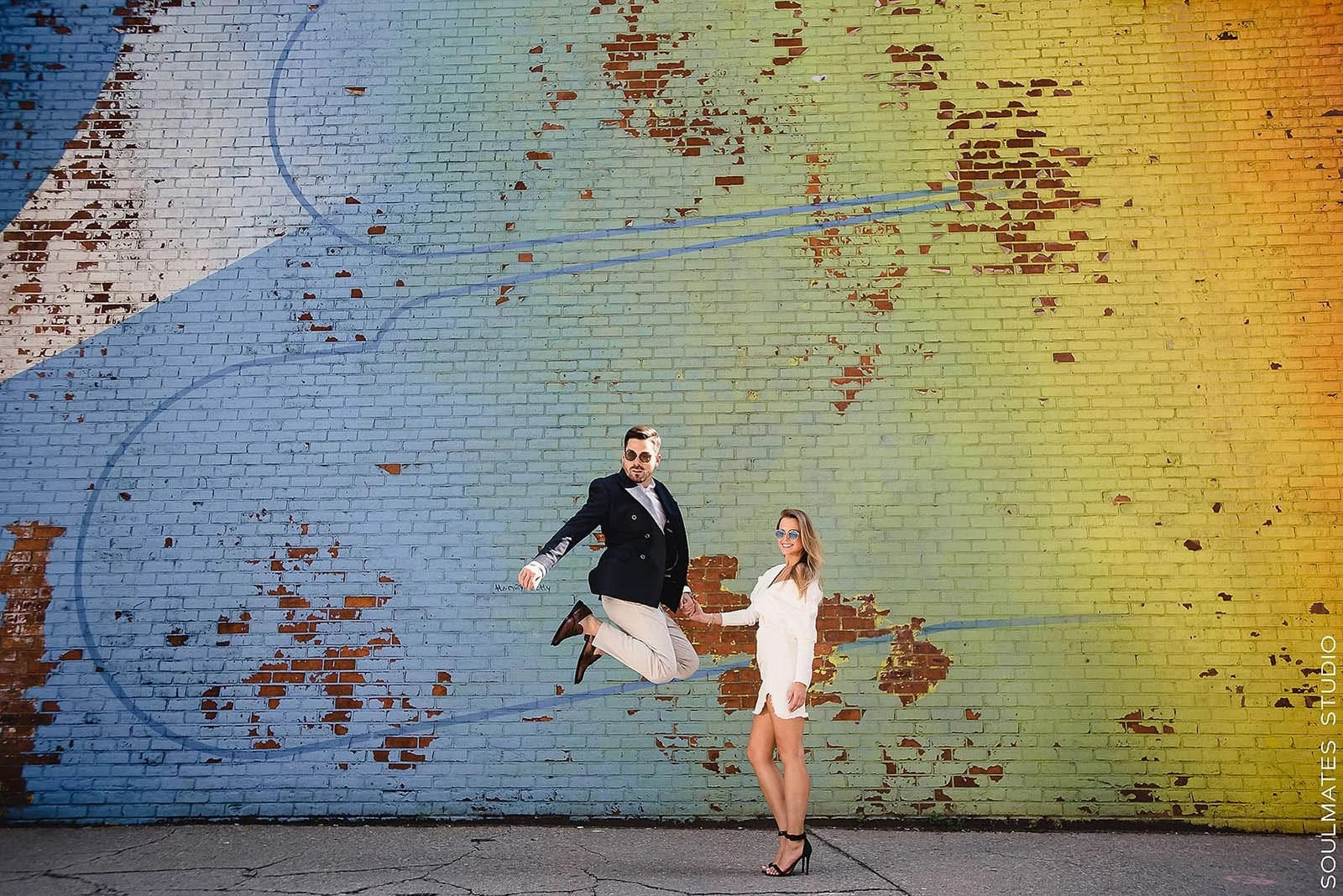 Groom to be jumping holding his fiance hand in front of the DUMBO graffiti wall