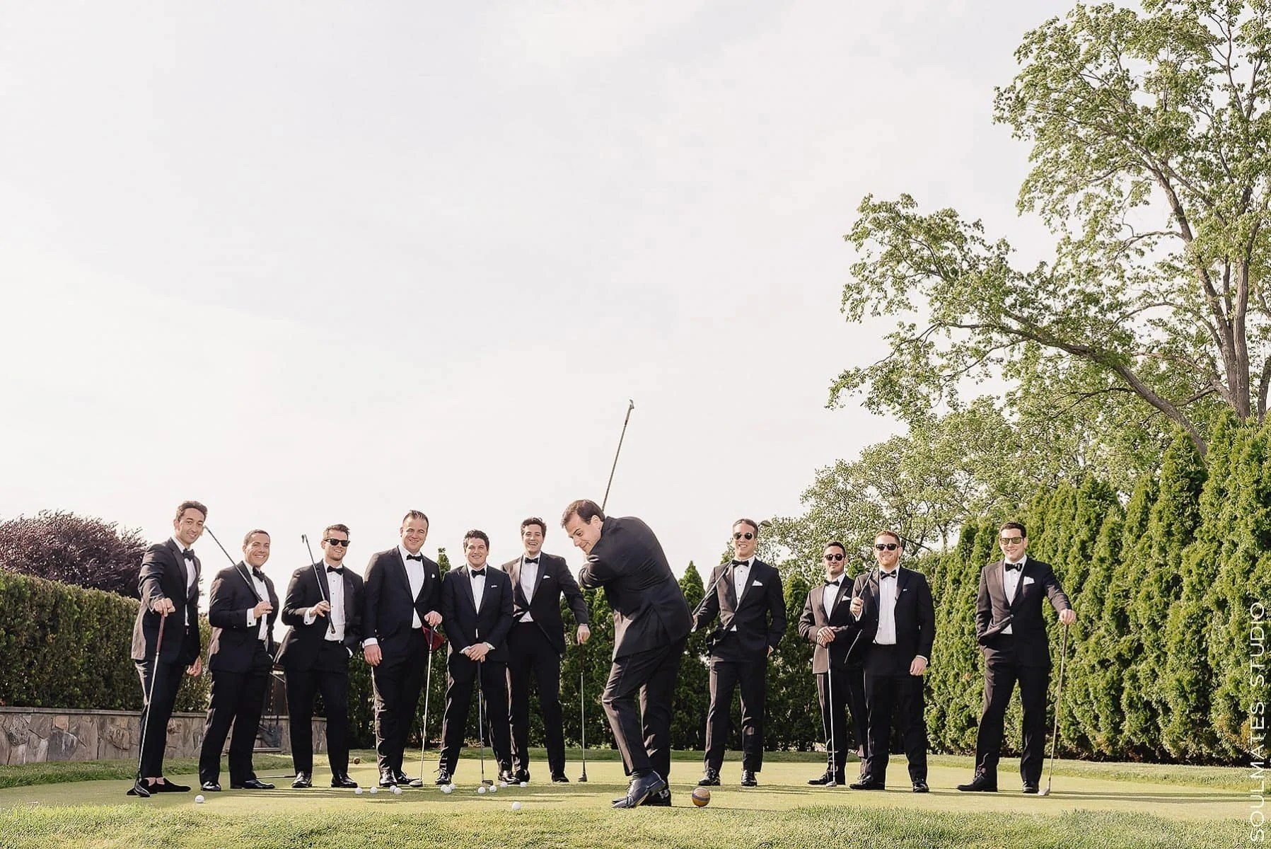 Groomsmen playing golf at Fresh Meadow Country Club
