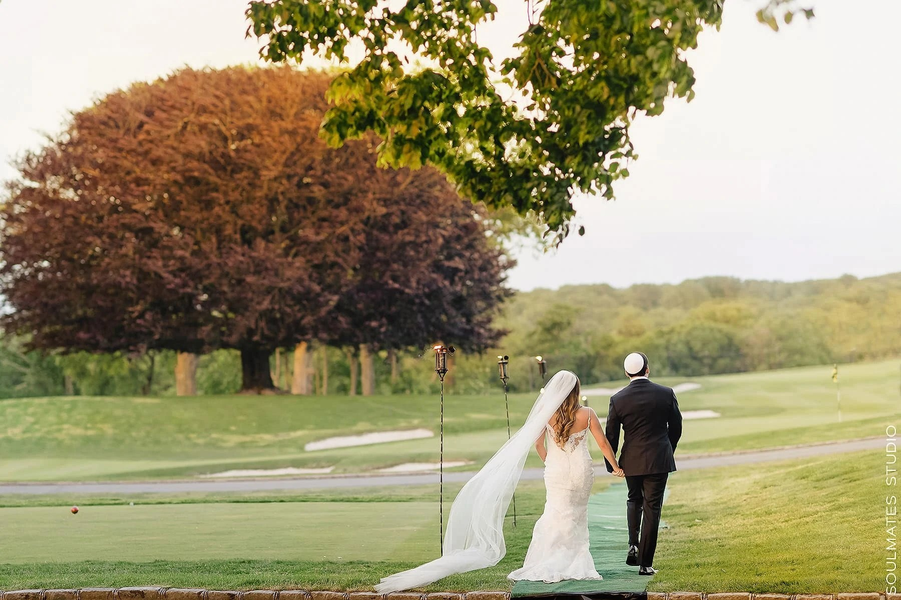 Bride and Groom walking out of the wedding ceremony location at Fresh Meadow Country Club