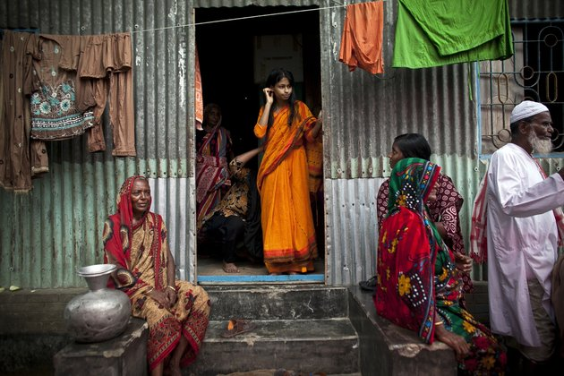 """MANIKGANJ, BANGLADESH - AUGUST 20: 15 year old Nasoin Akhter stands in the doorway of a neighbors home on the day of her wedding to a 32 year old man, August 20, 2015 in Manikganj, Bangladesh.  In June of this year, Human Rights Watch released a damning report about child marriage in Bangladesh. The country has one of the highest rates of child marriage in the world, with 29% of girls marrying before the age of 15, and 65% of girls marrying before they turn 18. The detrimental effects of early marriage on a girl cannot be overstated. Most young brides drop out of school. Pregnant girls from 15-20 are twice as likely to die in childbirth than those 20 or older, while girls under 15 are at five times the risk. Research cites spousal age difference as a significant risk factor for violence and sexual abuse. Child marriage is attributed to both cultural tradition and poverty. Parents believe that it """"protects"""" girls from sexual assault and harassment. Larger  dowries are not required for young girls, and economically, women's earnings are insignificant as compared to men's. (Photo by Allison Joyce/Getty Images)"""