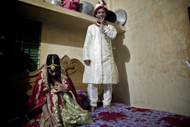 """MANIKGANJ, BANGLADESH - AUGUST 20: 32 year old Mohammad Hasamur Rahman stands on a bed above his new bride, 15 year old Nasoin Akhter, August 20, 2015 in Manikganj, Bangladesh.  In June of this year, Human Rights Watch released a damning report about child marriage in Bangladesh. The country has one of the highest rates of child marriage in the world, with 29% of girls marrying before the age of 15, and 65% of girls marrying before they turn 18. The detrimental effects of early marriage on a girl cannot be overstated. Most young brides drop out of school. Pregnant girls from 15-20 are twice as likely to die in childbirth than those 20 or older, while girls under 15 are at five times the risk. Research cites spousal age difference as a significant risk factor for violence and sexual abuse. Child marriage is attributed to both cultural tradition and poverty. Parents believe that it """"protects"""" girls from sexual assault and harassment. Larger  dowries are not required for young girls, and economically, women's earnings are insignificant as compared to men's. (Photo by Allison Joyce/Getty Images)"""