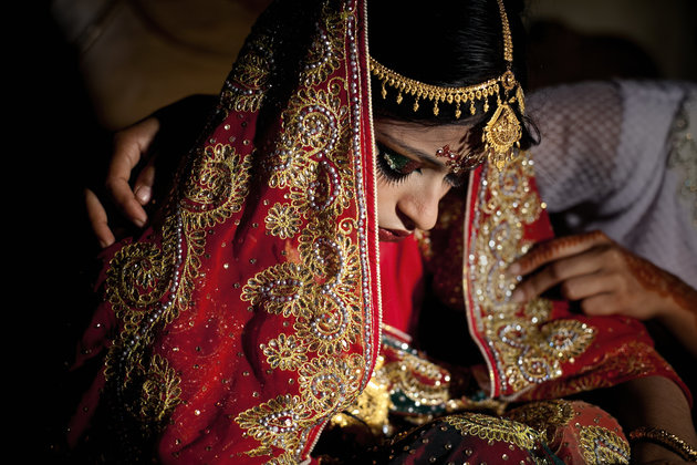 """MANIKGANJ, BANGLADESH - AUGUST 20: 15 year old Nasoin Akhter is consoled by a friend on the day of her wedding to a 32 year old man, August 20, 2015 in Manikganj, Bangladesh.  In June of this year, Human Rights Watch released a damning report about child marriage in Bangladesh. The country has one of the highest rates of child marriage in the world, with 29% of girls marrying before the age of 15, and 65% of girls marrying before they turn 18. The detrimental effects of early marriage on a girl cannot be overstated. Most young brides drop out of school. Pregnant girls from 15-20 are twice as likely to die in childbirth than those 20 or older, while girls under 15 are at five times the risk. Research cites spousal age difference as a significant risk factor for violence and sexual abuse. Child marriage is attributed to both cultural tradition and poverty. Parents believe that it """"protects"""" girls from sexual assault and harassment. Larger  dowries are not required for young girls, and economically, women's earnings are insignificant as compared to men's. (Photo by Allison Joyce/Getty Images)"""
