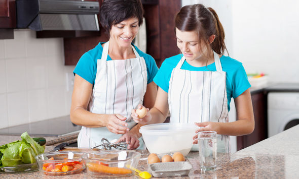 middle aged mother teaching teen daughter baking in kitchen