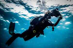 Diver with camera filming below the surface blue water