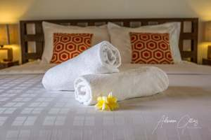 Inviting bed with towels and flowers in a hotel room