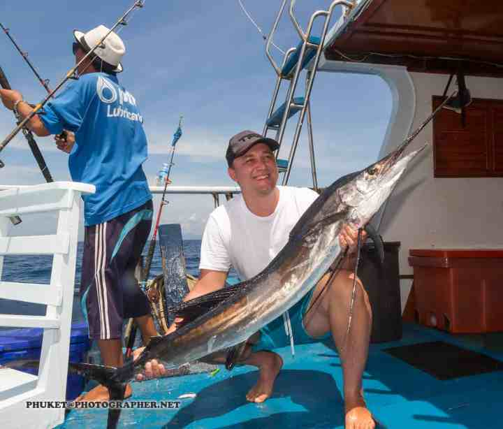 Fisherman on boat with huge marlin / sailfish catch and release