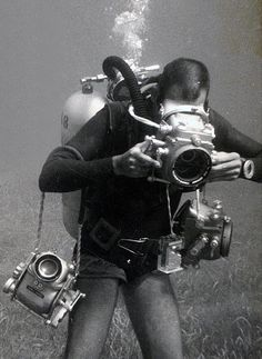 Diver with old fashioned cameras and dive equipment, double hose regulator, black and white