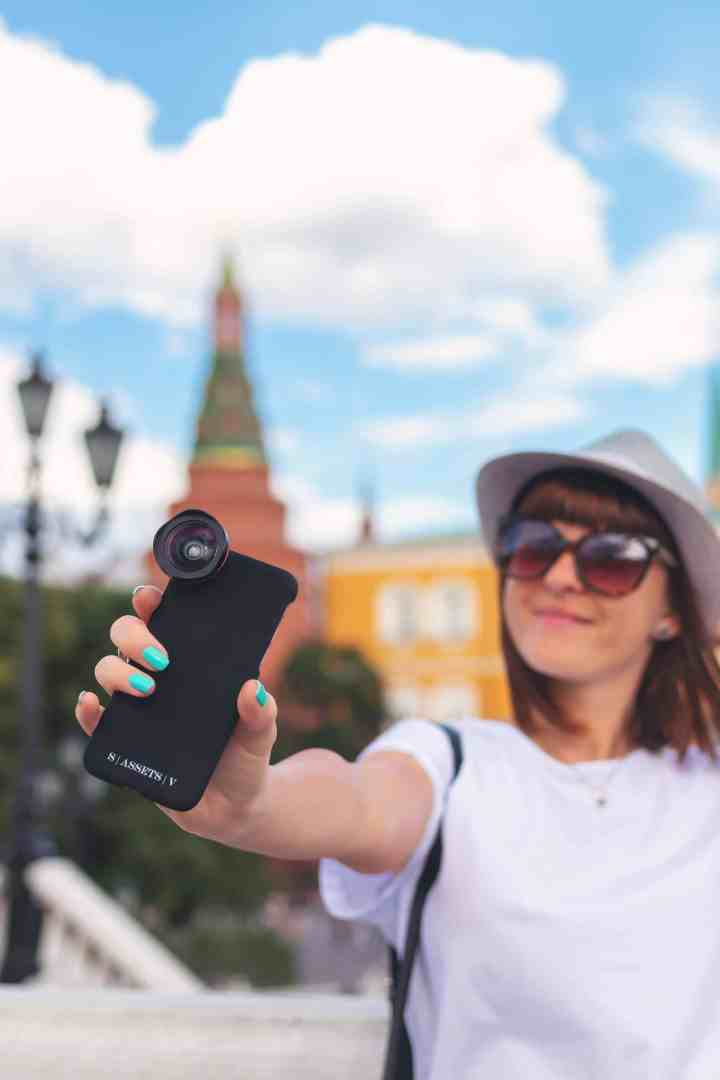 Woman taking selfie with camera with wide angle lens