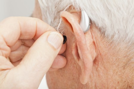 Close up of senior man's ear with hearing aid