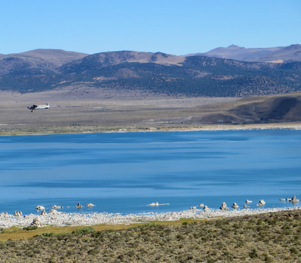Single engine airplane flying low over Mono Lake