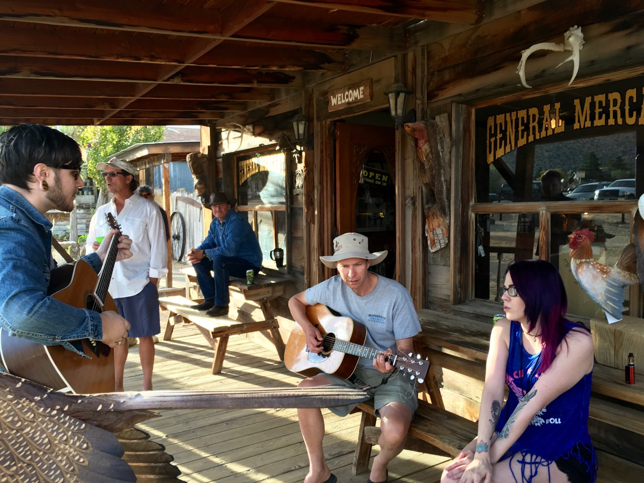 Two men playing guitar, woman singing outside Chaparrosa Outfitters, Pioneertown