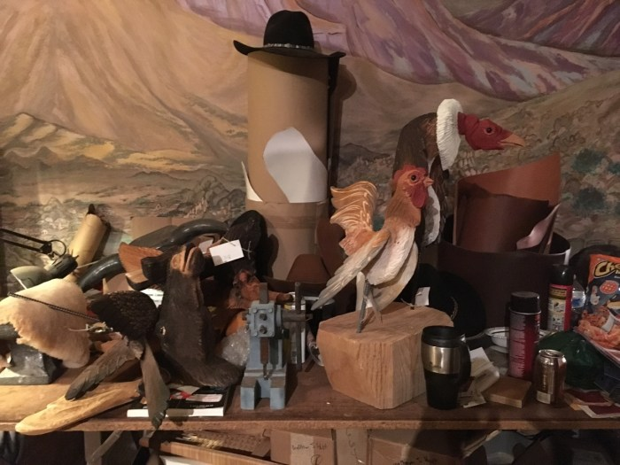 Chaparrosa Outfitters workbench detail, carved wooden chicken, vulture, leather scraps and hat