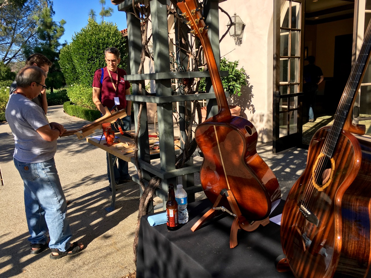 Handmade guitars outside with man demonstrating construction at Fretboard Summit